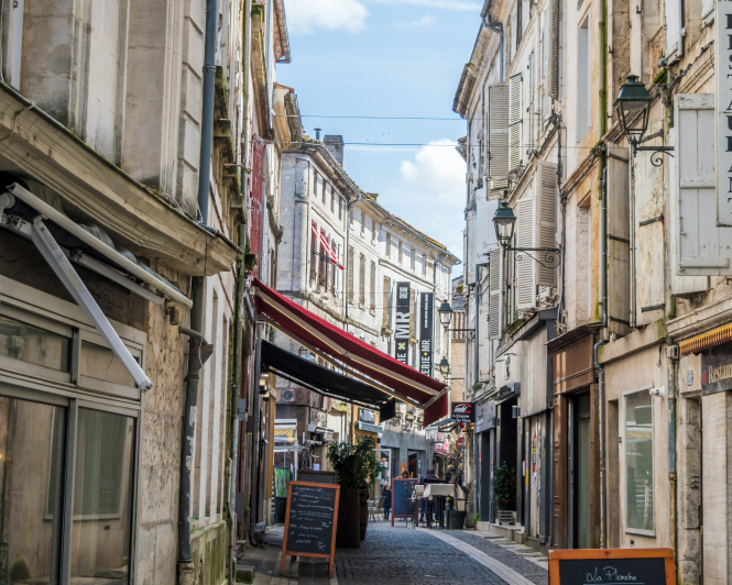A cobbled street with restaurants in Angoulême, France. Angoulême lengthened its runway to attract Ryanair. Jaël Vallée / Unsplash.