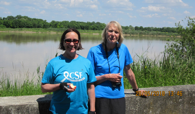 Two women in blue T-shirts in front of stretch of water