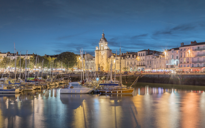 La Rochelle old port at dusk, with boats on the water and buildings lit up. Karim Manjra/Unsplash