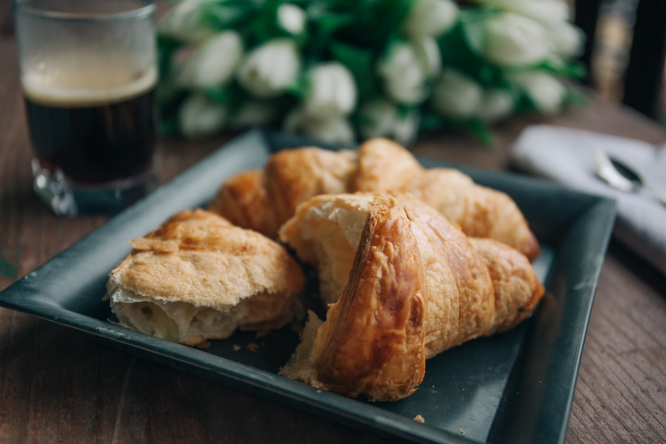 A croissant and espresso on a wooden table.