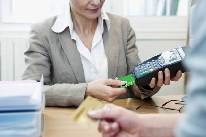 A woman inserting a carte vitale into a payment machine