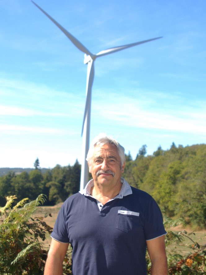 Man stands in front of wind turbine on hill
