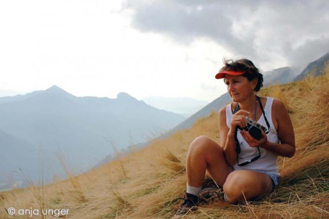 Teresa Kaufman sits on a grassy mountain ready to take photograph