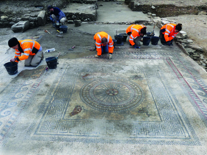 Four workers in orange jackets work to uncover a large mosaic