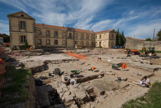 Ground level view of archaeological dig with building in background