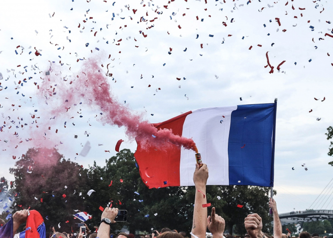 People hold French flags at a celebration in Strasbourg, France.