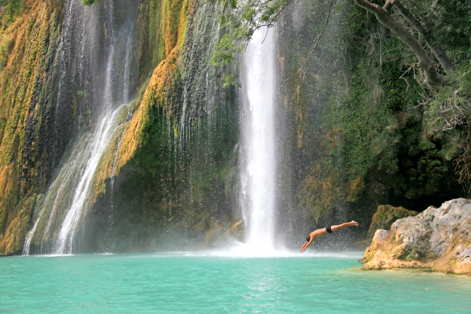waterfall with person diving into pool
