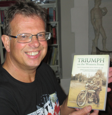 Bespectacled man with book with sepia image on front