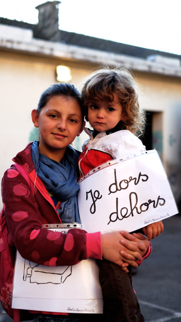 """Refugee children in Annecy hold up a sign that reads, in French, """"I sleep outside"""""""