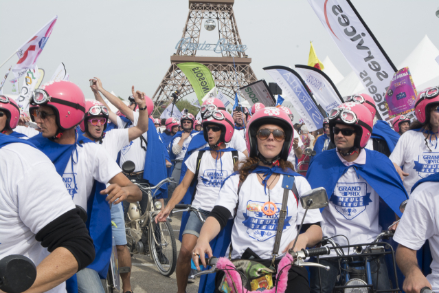 People in white T-shirts, pink crash helmets and blue capes gather on Mobylettes
