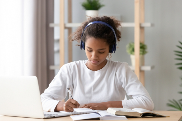 A child working at a laptop. Our guide to how to find extra help with schoolwork in France