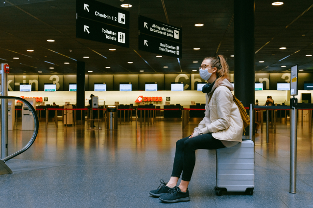 A woman sits on her suitcase wearing a mask at an airport