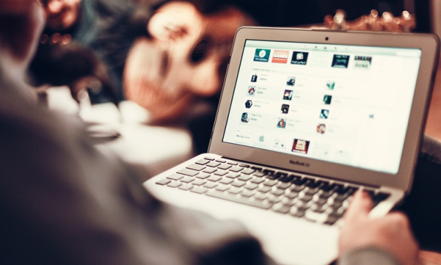 Man sits at open laptop with screen full of icons internet shopping Mac