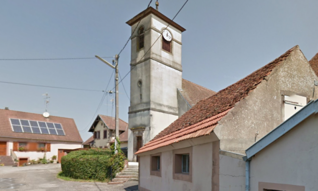 Church tower in Asswiller, Bas-Rhin with some surrounding buildings. Bright day