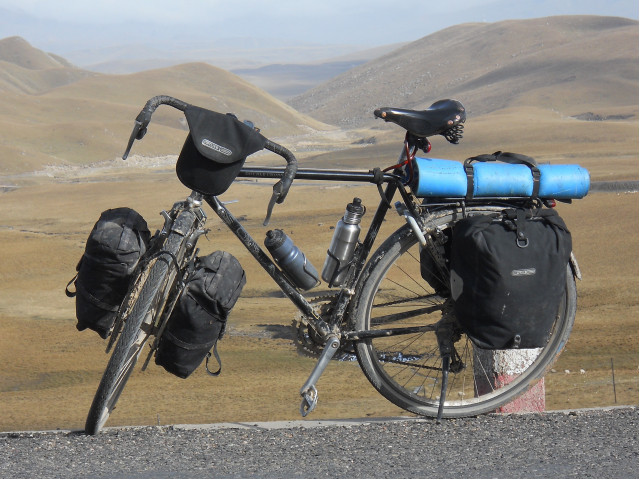 Dark bicycle loaded with luggage for touring