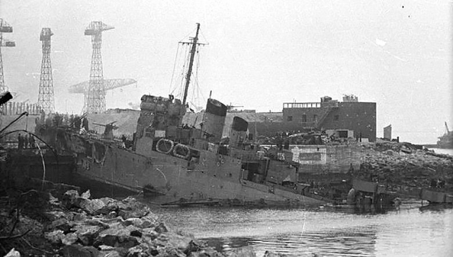 Black and white photo of destroyer wrecked in port