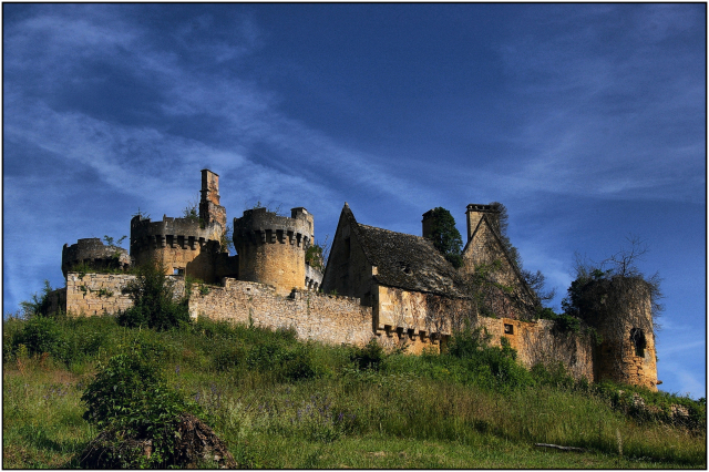Fortress-type chateau with green hilly foreground and blue cloud-streaked sky
