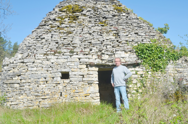 Dry-stone huts expert Jean-Marc Caron standing in front of Cabane du Mazut