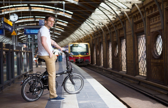Man sits on folding bicycle in rail station