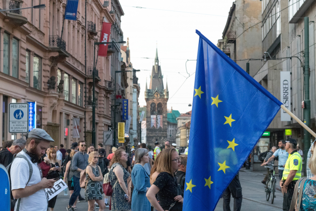 An EU flag is waved in a busy city centre