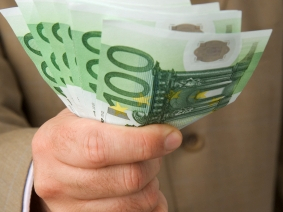 Man's hand holding a fistful of €100 notes