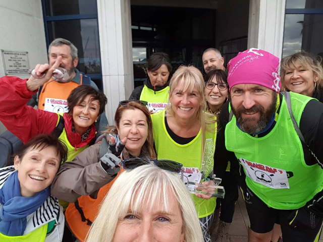 Group of smiling people, some in yellow or orange vests for selfie