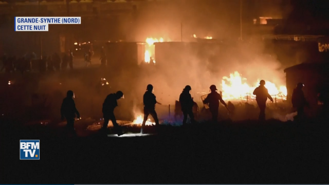 Helmeted people walking in front of fires on a dark night