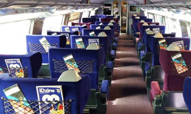 View up corridor of empty purple coloured seats on IDTGV train. Seat have magazines on backs