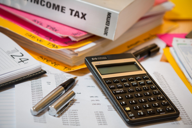 A calculator, paperwork and an income tax guide