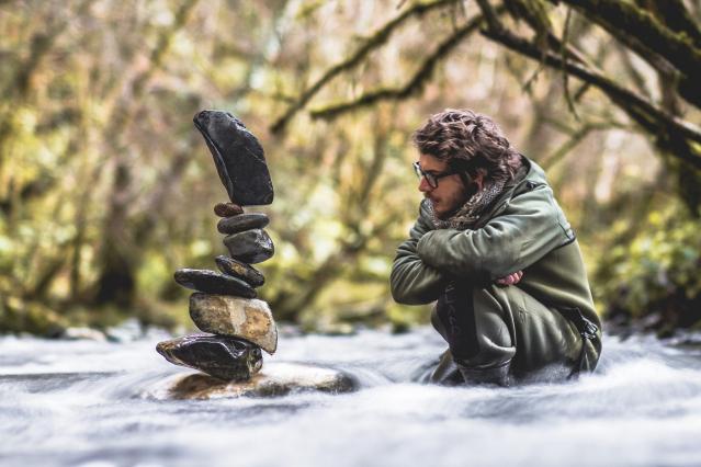 Man admires stone sculpture in stream in woods