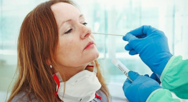 a woman gets a nasal swab to test for Covid-19