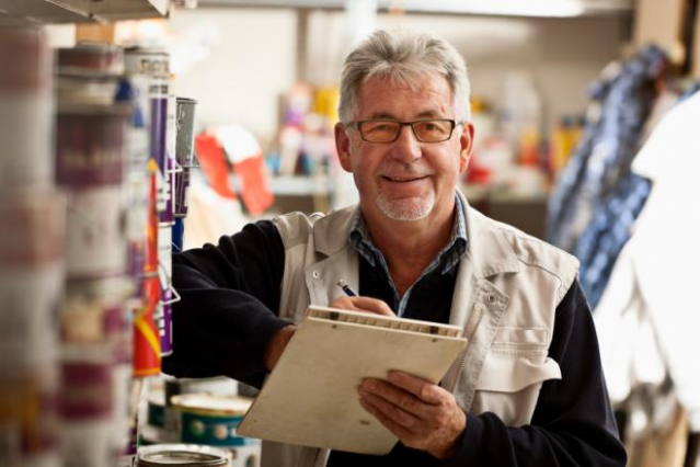 older worker smiling in shop environment
