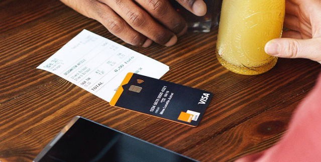 Glass of orange juice, a cafe bill and a credit card