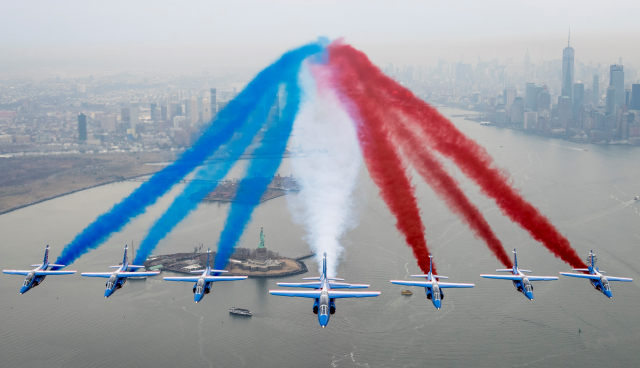 A line-up of jets with blue, white and red smoke billowing behind them over the Statue of Liberty and Manhattan