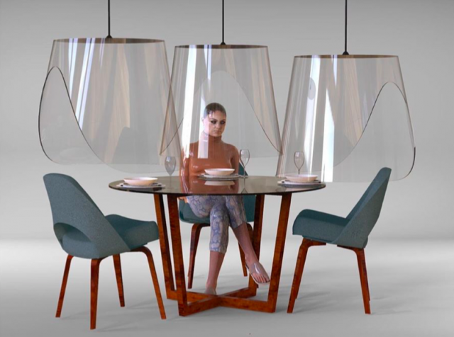 A woman sits under a transparent plexiglas dome at a dining table. Plex'eat is a design by Christophe Gernigon. Image via Instagram.