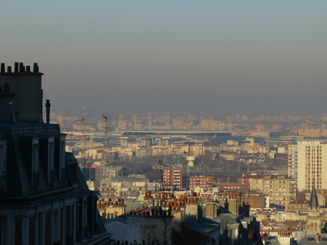 Shadowed building on left with view over Paris suburbs clouded by pollution