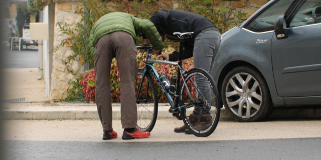 Men bend over bicycle