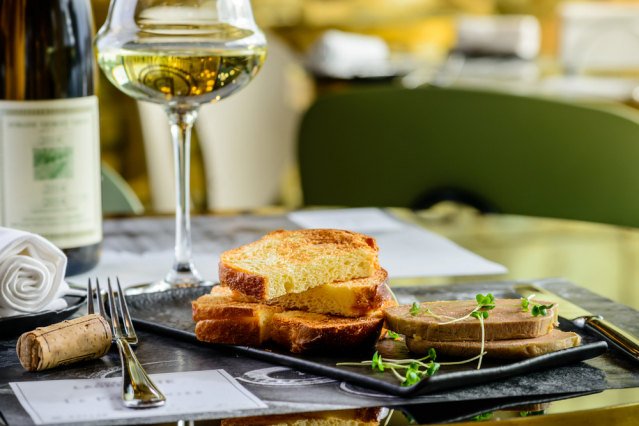 Foie gras served with toast and a glass of wine at a restaurant