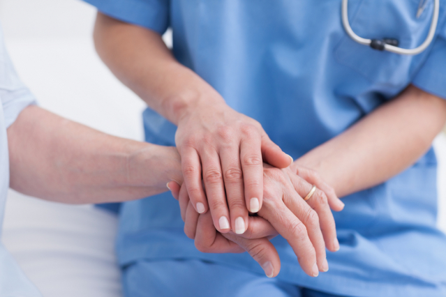 Nurse holding patient's hand in hospital