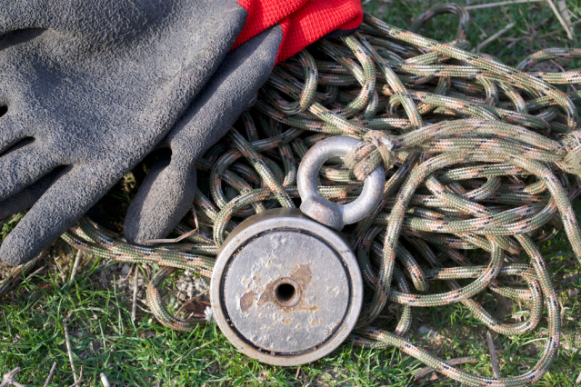 Fishing magnet, rope and gloves on grass