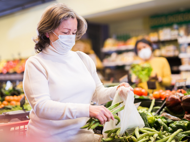 Mature woman in protective mask choosing beans at grocery store