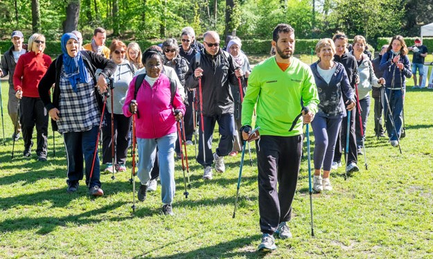 A fitness leader takes a large group of people Nordic walking with poles - trees in background