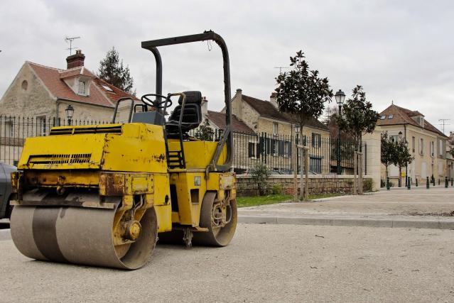 Yellow steam roller in street background