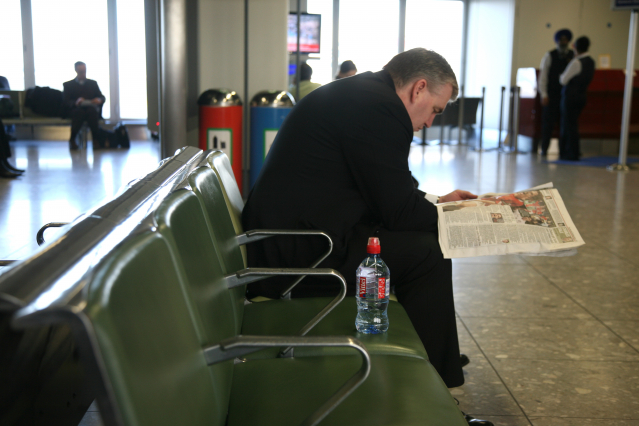 A man reads a newspaper in an airport