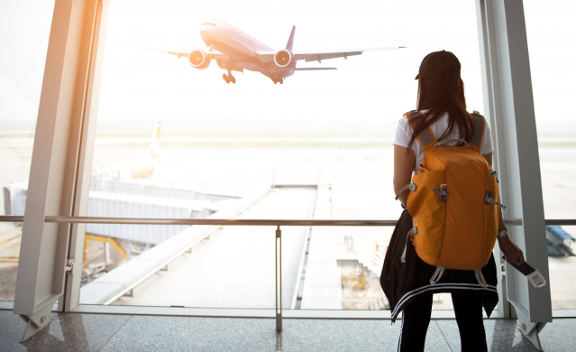 A young woman looks out of the airport window at a plane taking off