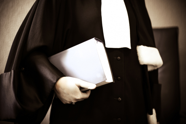 an avocat in robes carries a book