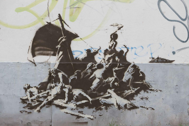 Banksy street art on a wall in Calais