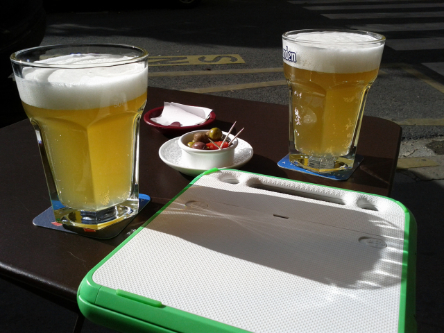 Two full glasses of beer on a table outside a bar in France