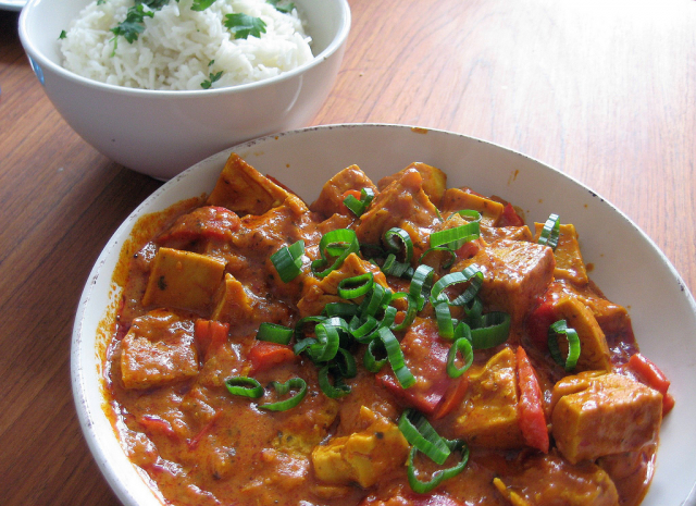 Image of a dish of popular Indian restaurant dish chicken tikka masala and another dish of cooked white rice