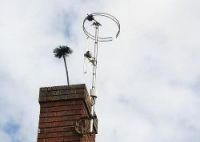 A sweep's brush sticks out of the top of a brick chimney against a cloudy sky